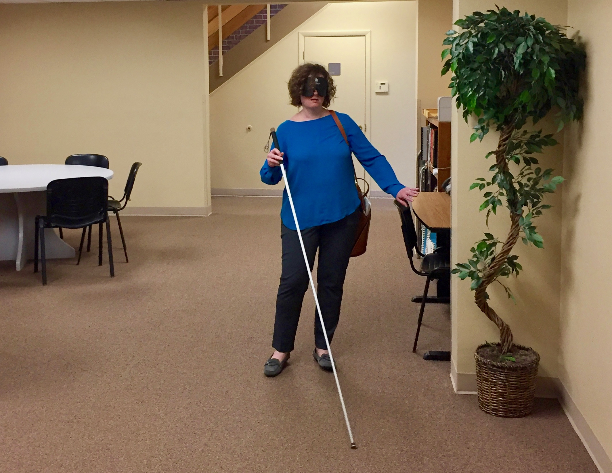 a woman wearing sleep shades uses her cane to maneuver in the  Travel Lobby.