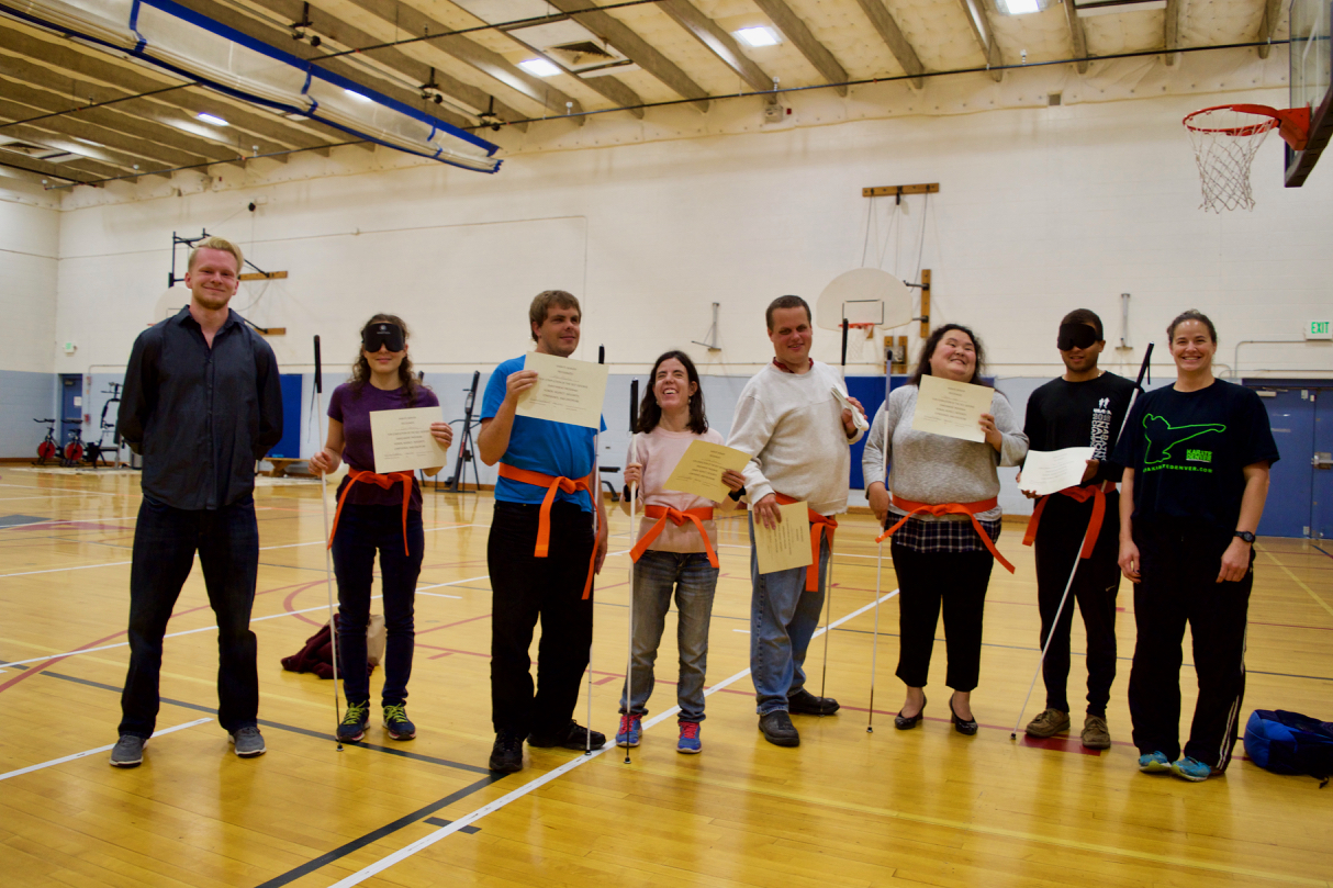 six class members stand in a semi-circle wearing their new Orange belts and hold certificates, flanked by two Karate Denver instructors