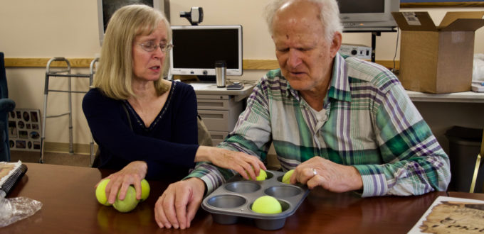 Steve works with Janet to learn the Braille Alphabet using a muffin tin and tennis balls