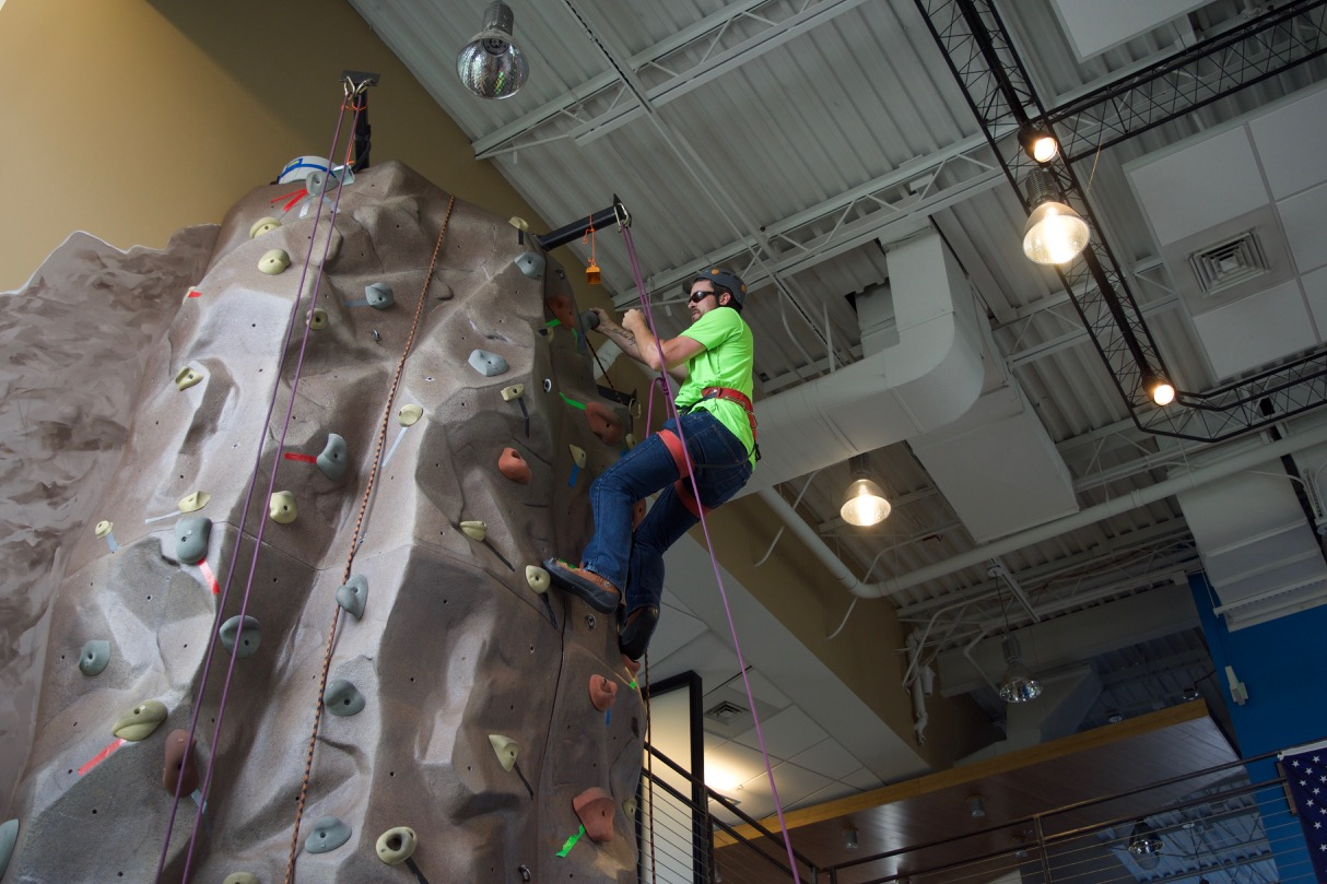 Zach P. reaches the top of the climbing wall and reaches for the bell