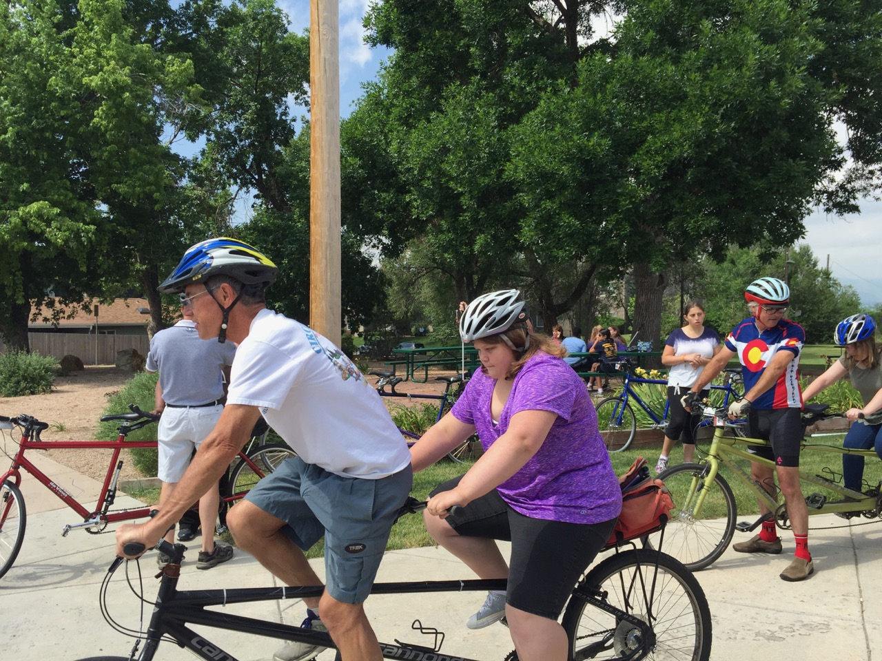 Volunteers steady tandem bicycles as students get aboard