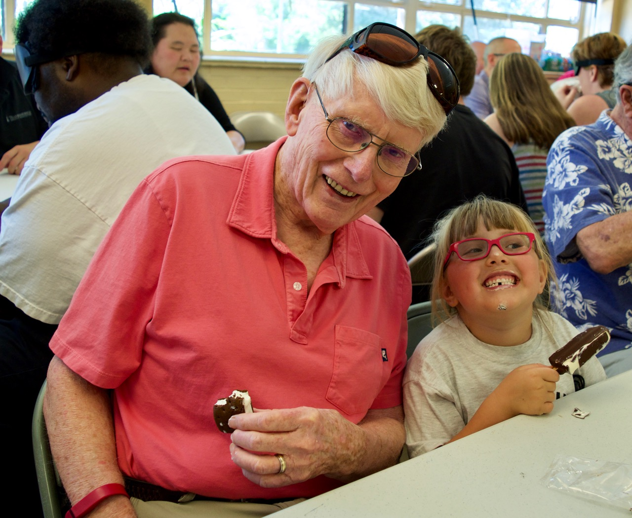 A man in his eighties sits beside a 6-year-old girl, both enjoying ice cream