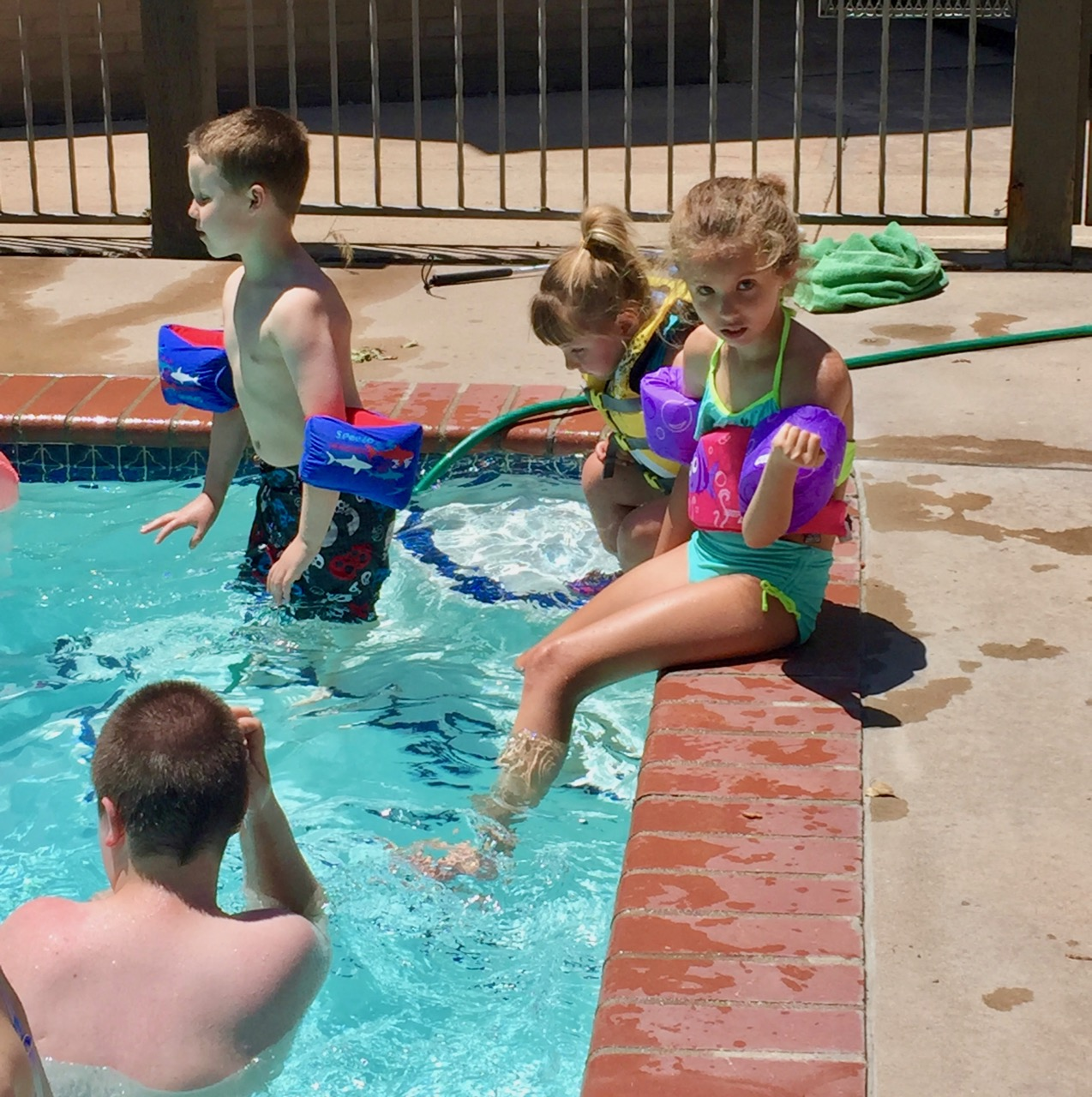 two little girls dangle feet into the pool