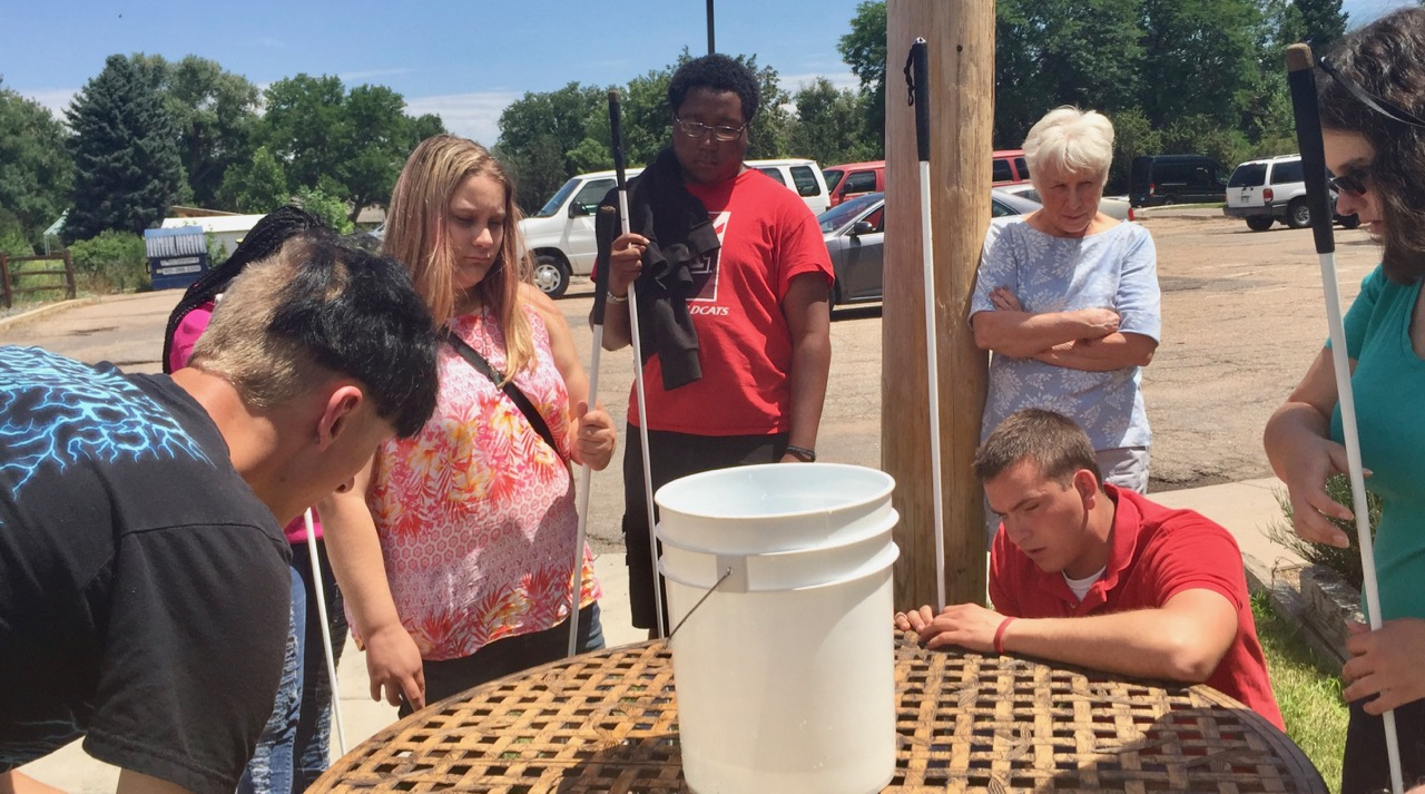 Ashley simulates how a tornado looks using a bucket and water, with Roland, Faye and Keishawn. Our volunteer Kaylooks on.