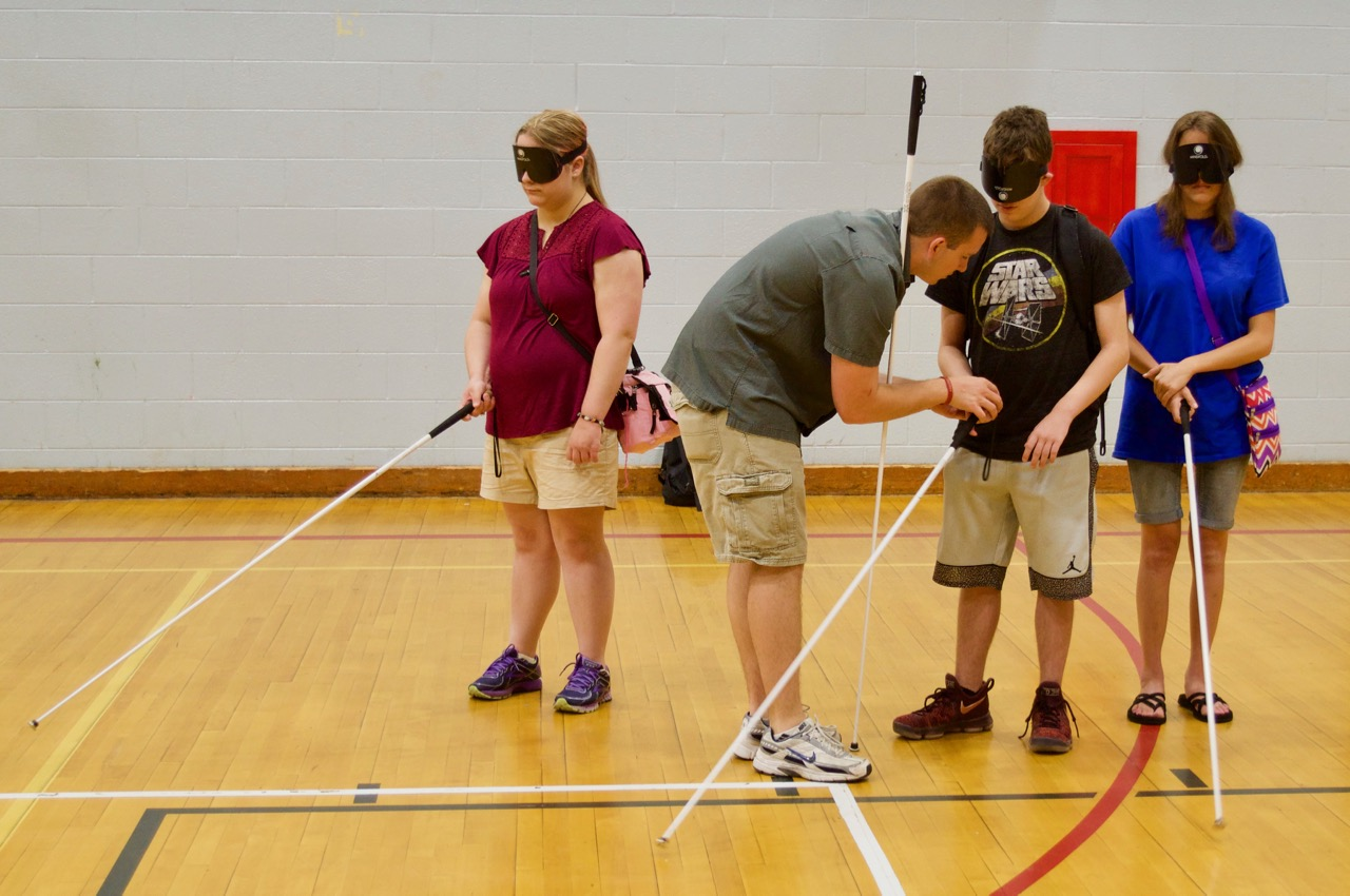 Garret works with 3 summer students in the Gym on holding their canes properly