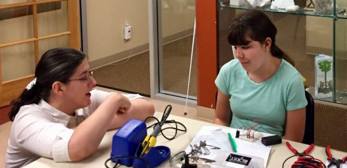 Jamie talks to Maddie while she works with a breadboard