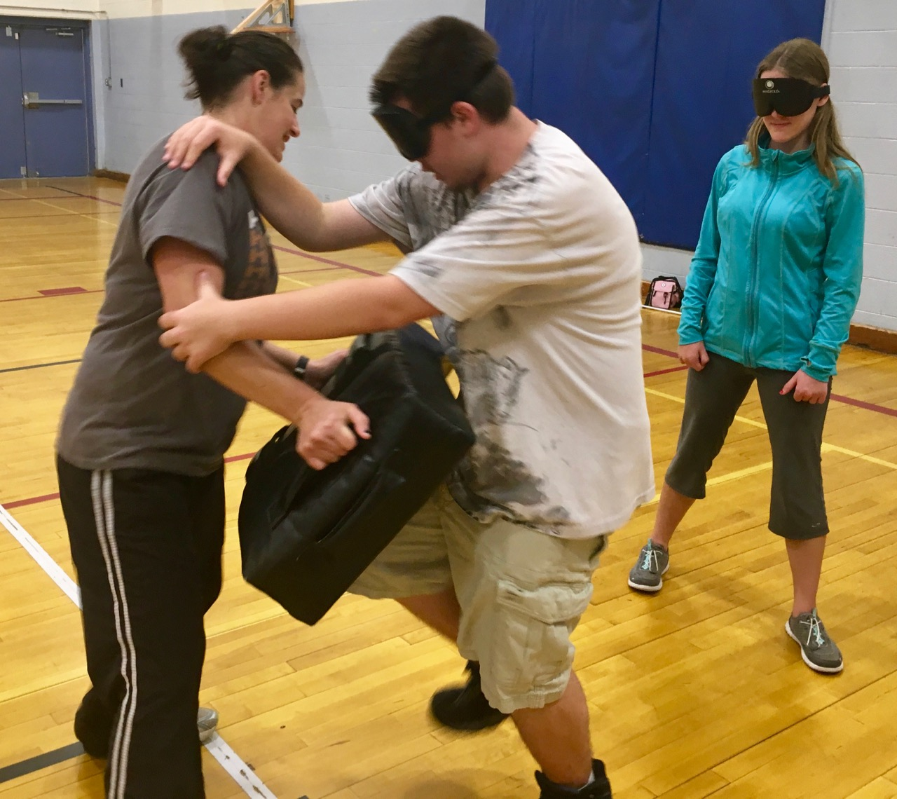 Masson learns how to put power in forward knee strikes while Rachael holds the pad. Maggie waits her turn to give it a try
