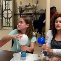 Maggie and Lauren experiment with chemically inflating balloons