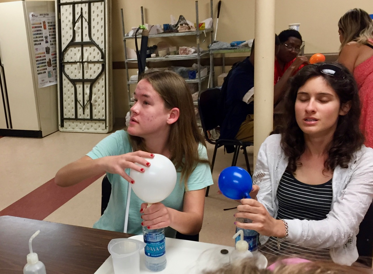 Maggie and Lauren watch as as their experiment produces gas that inflates balloons