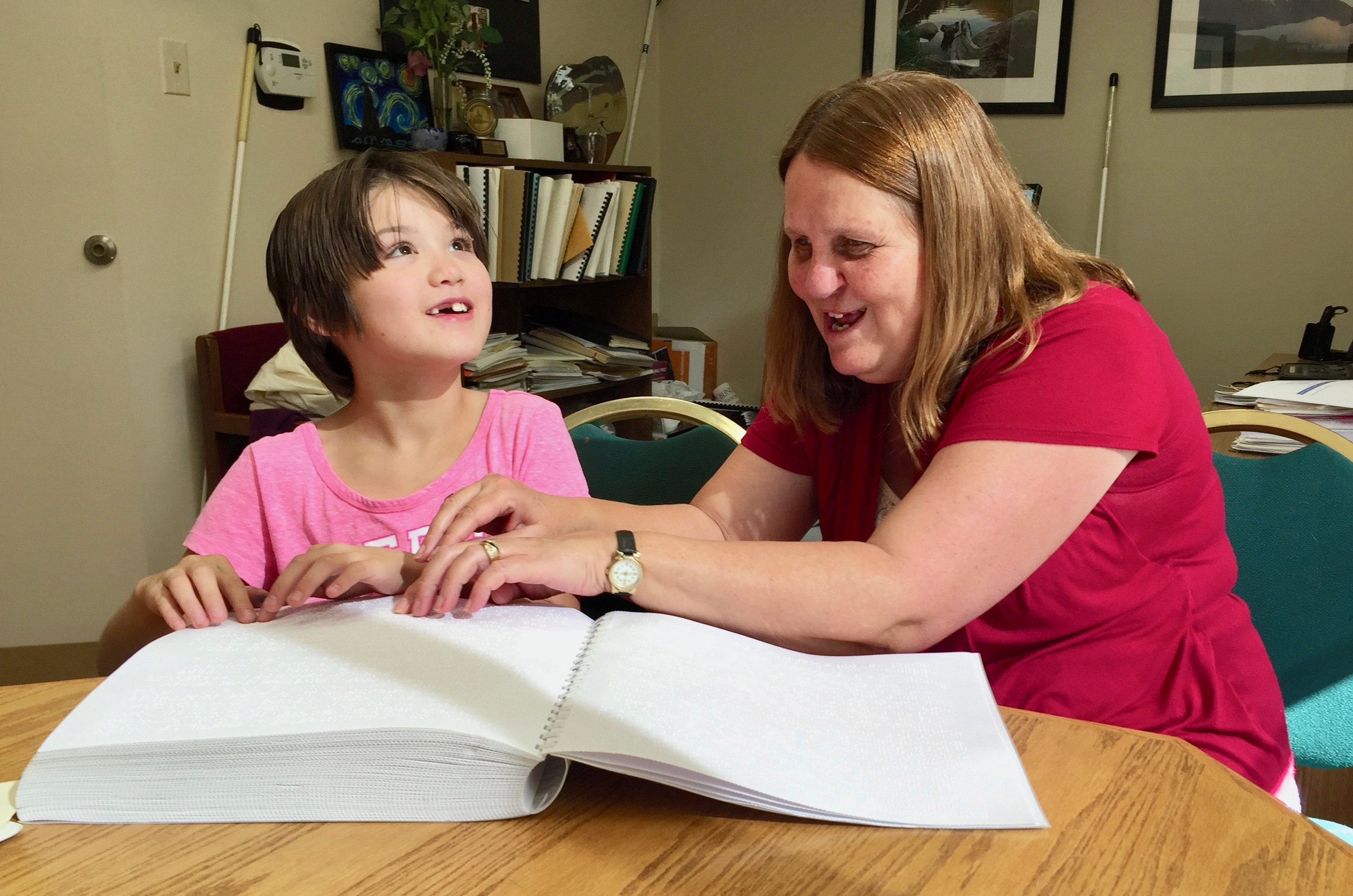 a smiling girl with missing front teeth and a woman with their hands on the same page of Braille
