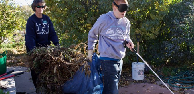 Tyler leads the way as he and Master Gardener Volunteer Barb P. carry a tarp loaded with stems and leaves pulled up from the garden