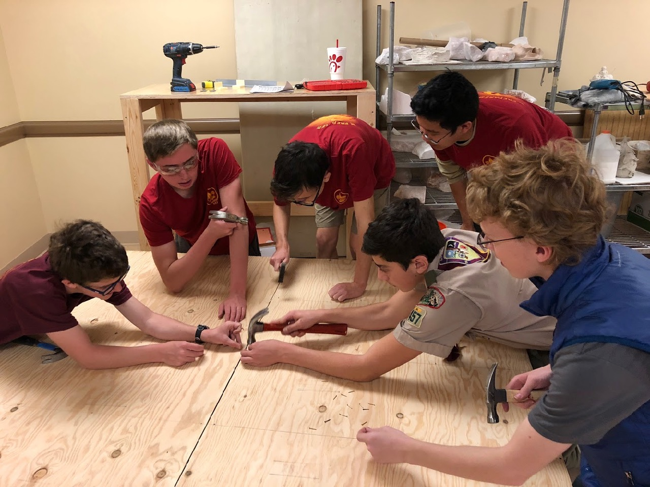 Alex LaBarre center with Lucas, Stephen, Scott, Kevin and Devin all hammering nails to secure two bench tops pictured side by side