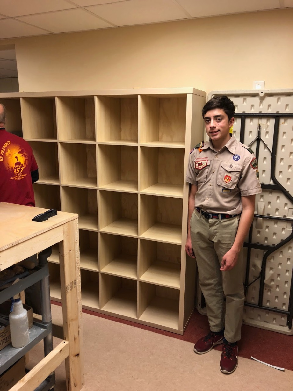 Alex LaBarre stands next to the new cubby shelves that he helped assemble for the art room