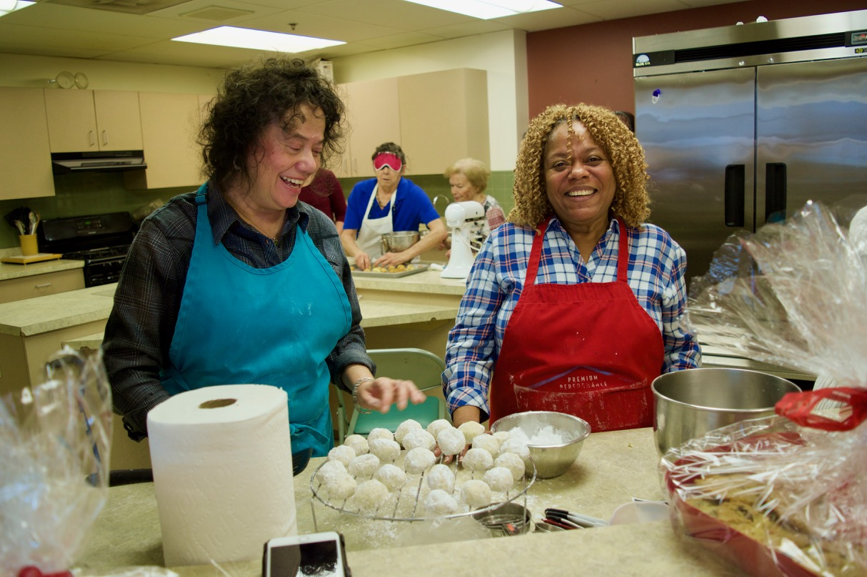 Blanca and Priscilla wearing festive colored aprons prepare a rack of home made powdered sugar cookies