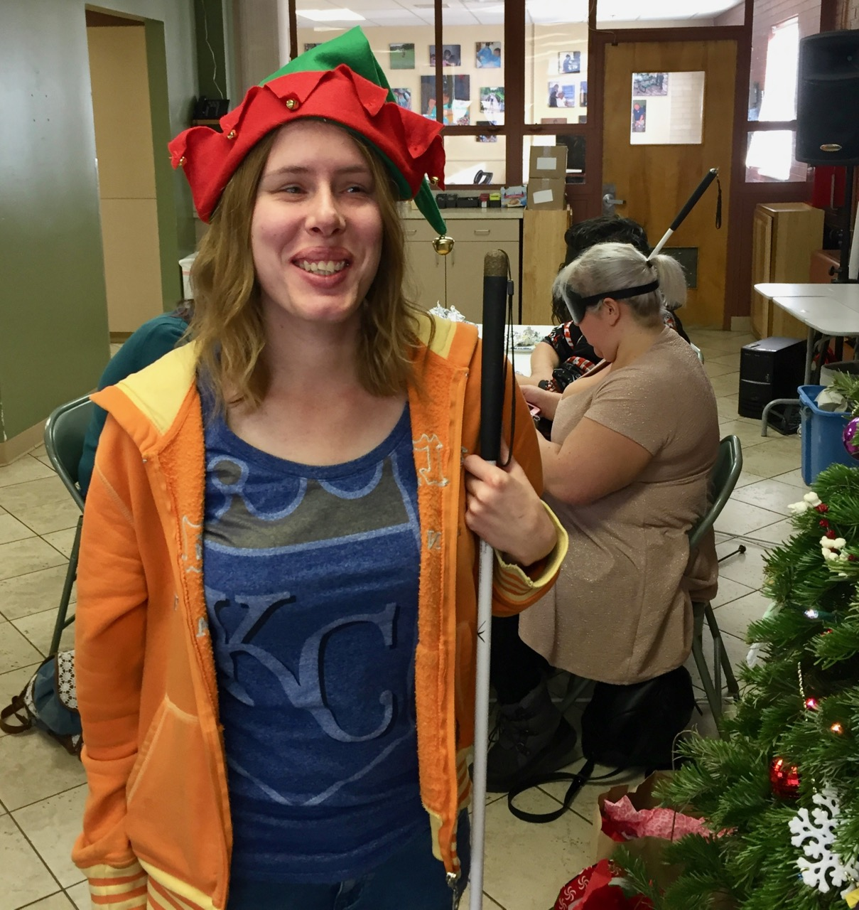 Holly wears a colorful elf hat with bells and smiles while standing next to the Christmas Tree