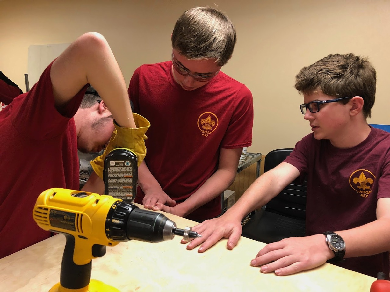 Jonathan uses a drill to secure the bench top while Stephen and Lucas hold everything in place