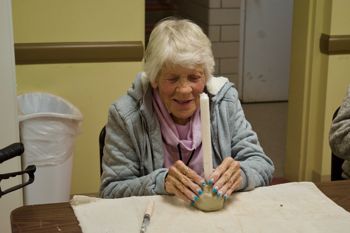 Judi fits a tall white candle into a clay base she is shaping into a candle holder