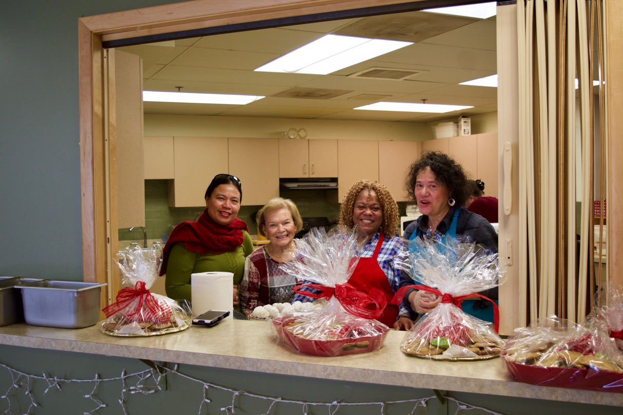 Mary Ann, Priscilla and Blanca in the Serving window with lots of finished trays of cookies wrapped up and tied with ribbons