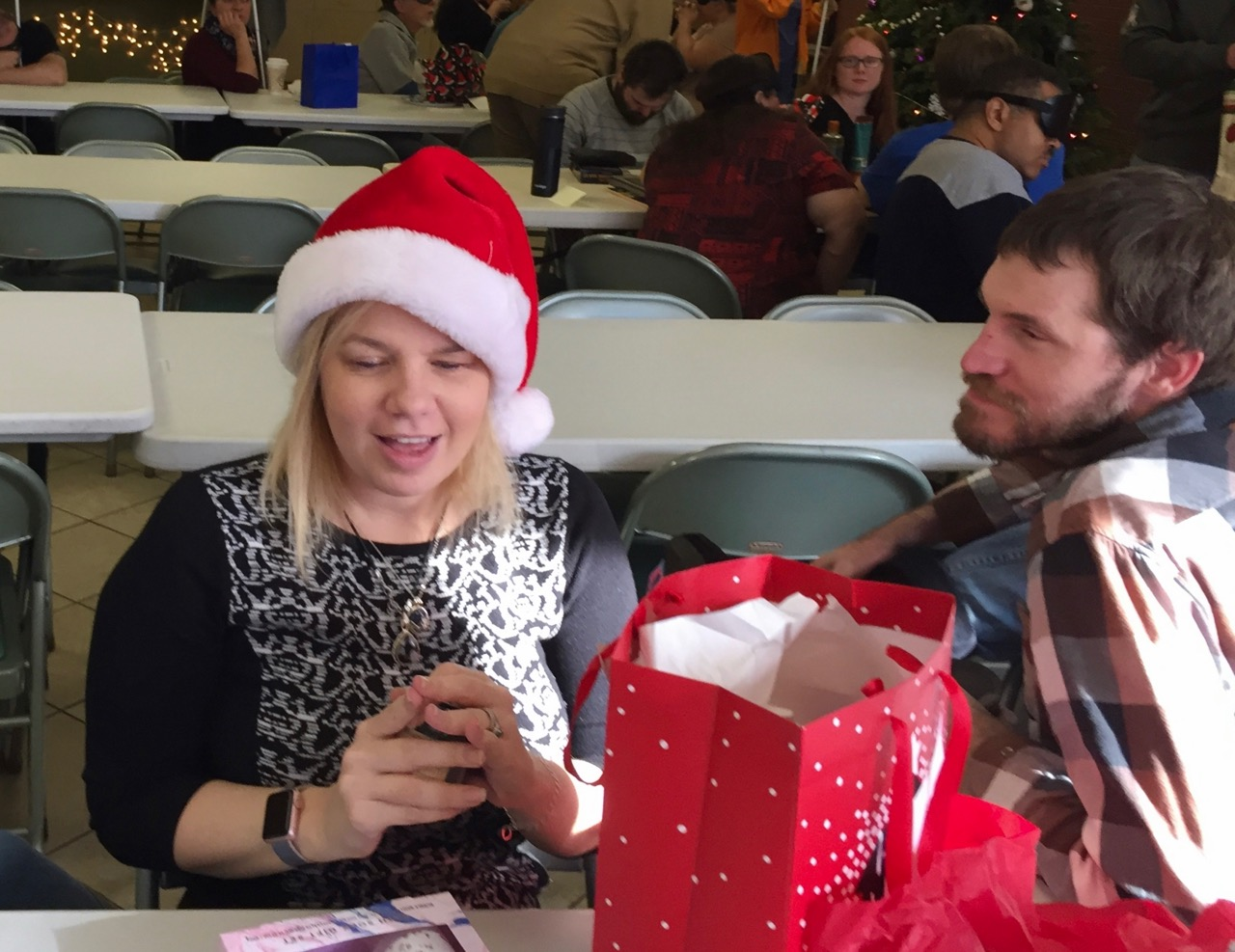 Maureen wearing her Santa hat opens her gift while David looks on