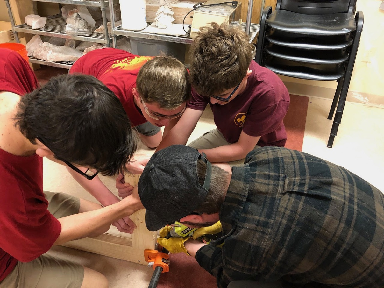 Scott, Stephan, Lucas and Jonathan work together on the floor to attach a leg to the top of one of the new benches
