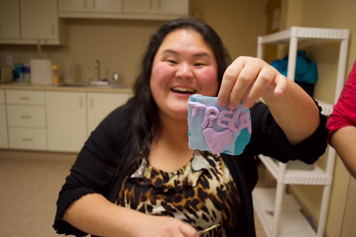 Showe holds up a clay ornament she made that spells out Trela with a heart underneath