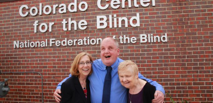 Duncan, Tom and Diane hug in front of the CCB sign on a bright spring day.