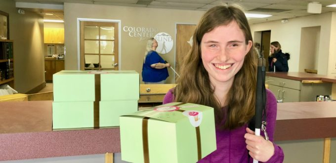 Rebecca beams a smile as she holds up a box of her Birthday cupcakes