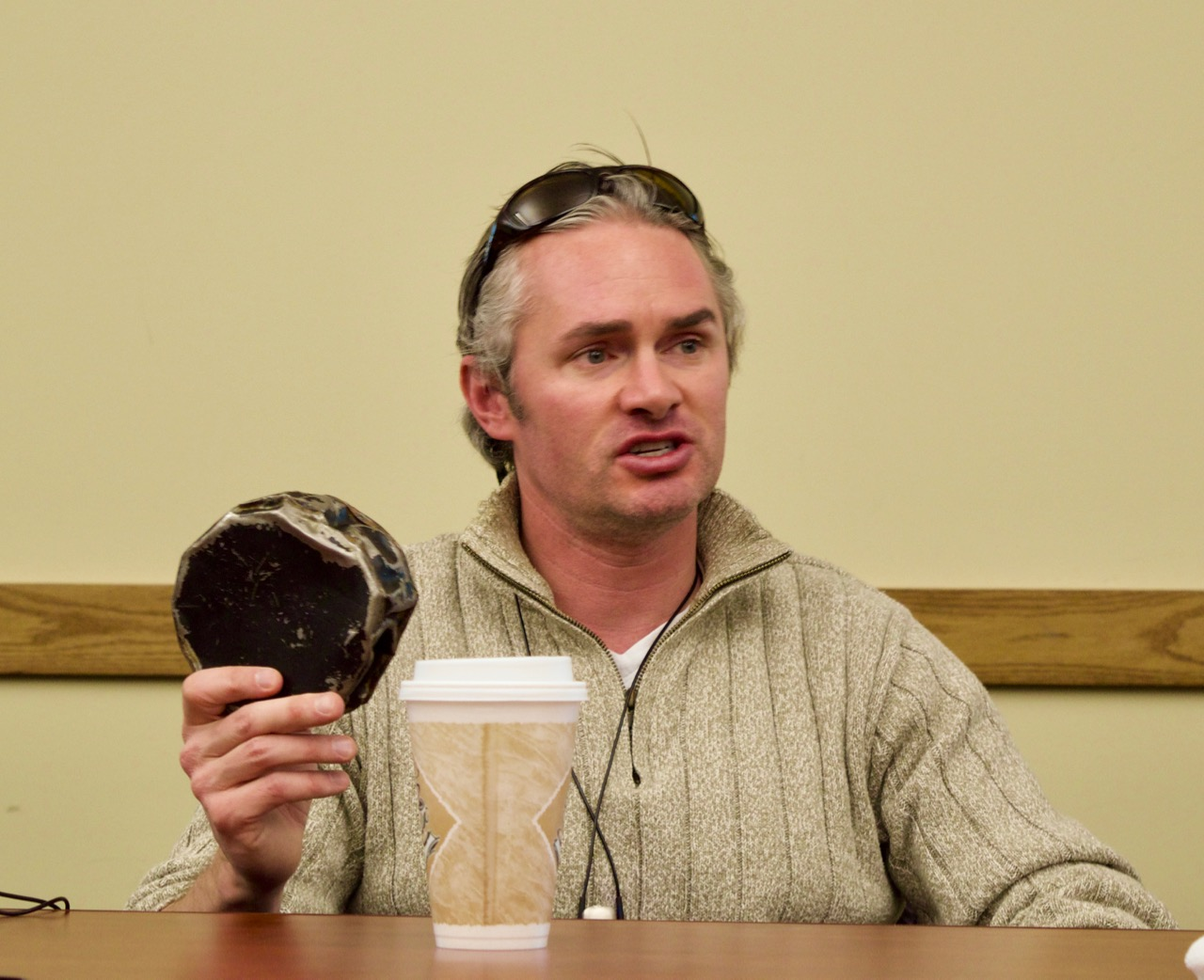 Craig Fitzpatrick holds up an adapted hockey puck while he gives a talk about Blind Hockey at the Colorado Center for the Blind