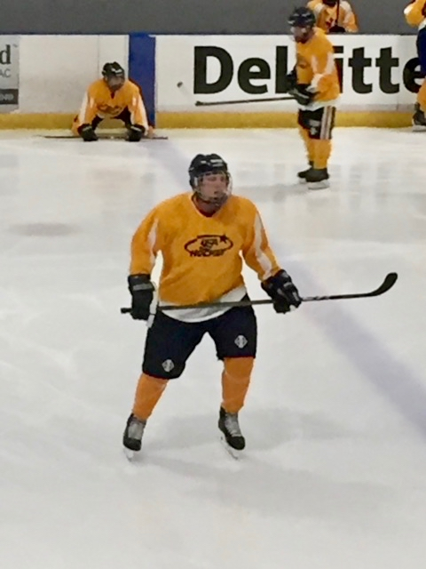 Daniel in full Hockey gear in action on the ice