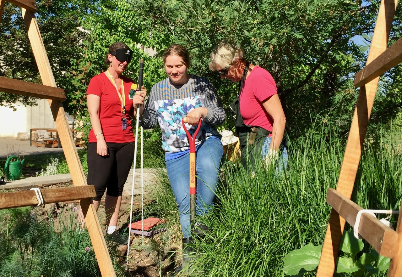 Amber turns dirt over in the garden with Annette and Master Gardener Barb