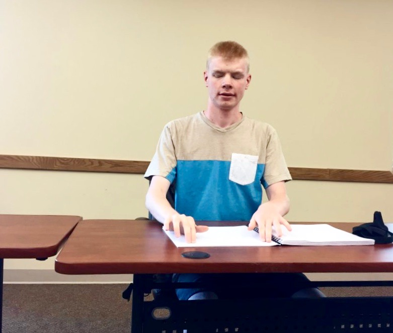 Luther Fuller of Kansas reading Braille before the National Braille Challenge