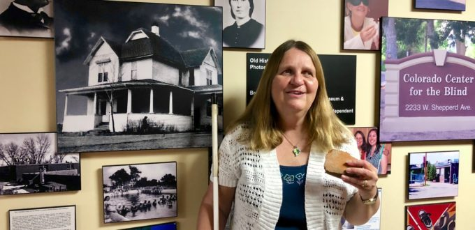 A smiling Julie holds a piece of broken red brick as she stands in front of a wall of black-and-white photos.