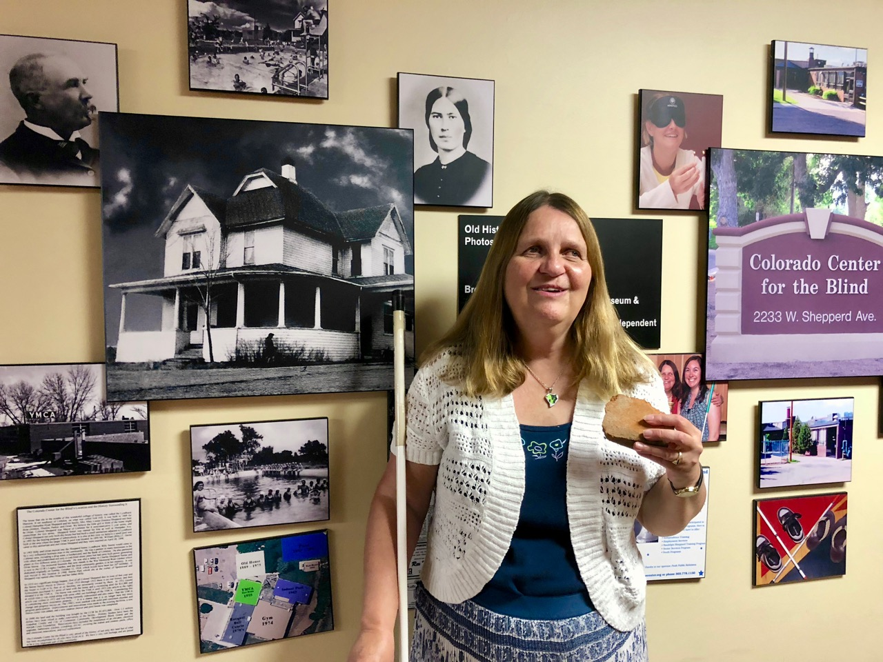 A smiling Julie Deden holds a piece of broken red brick as she stands in front of a wall of black-and-white photos.
