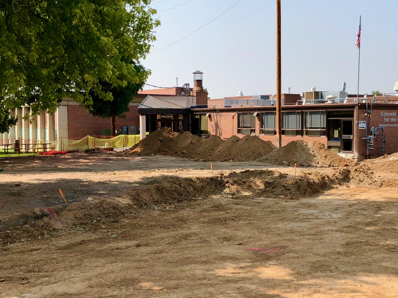 A view of the torn up parking lot in front of the Colorado Center for the blind with excavation trenches and tall mounds of dirt
