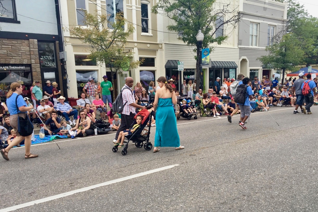 Two Blind Parents pull their son in a stroller as they march in the parade