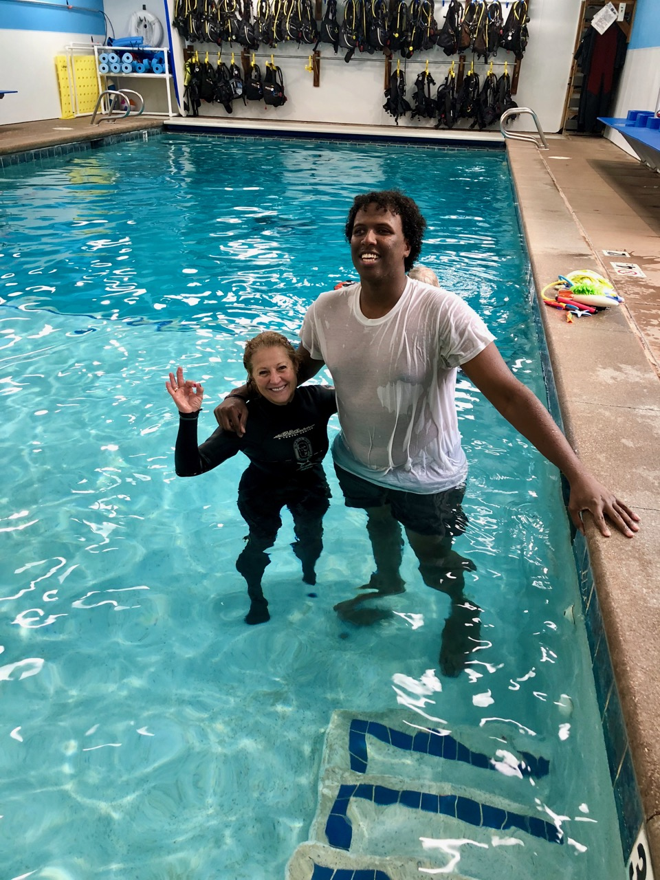 A tall young man in t-shirt stands with his petite, wet-suited instructor in the shallow end of the pool