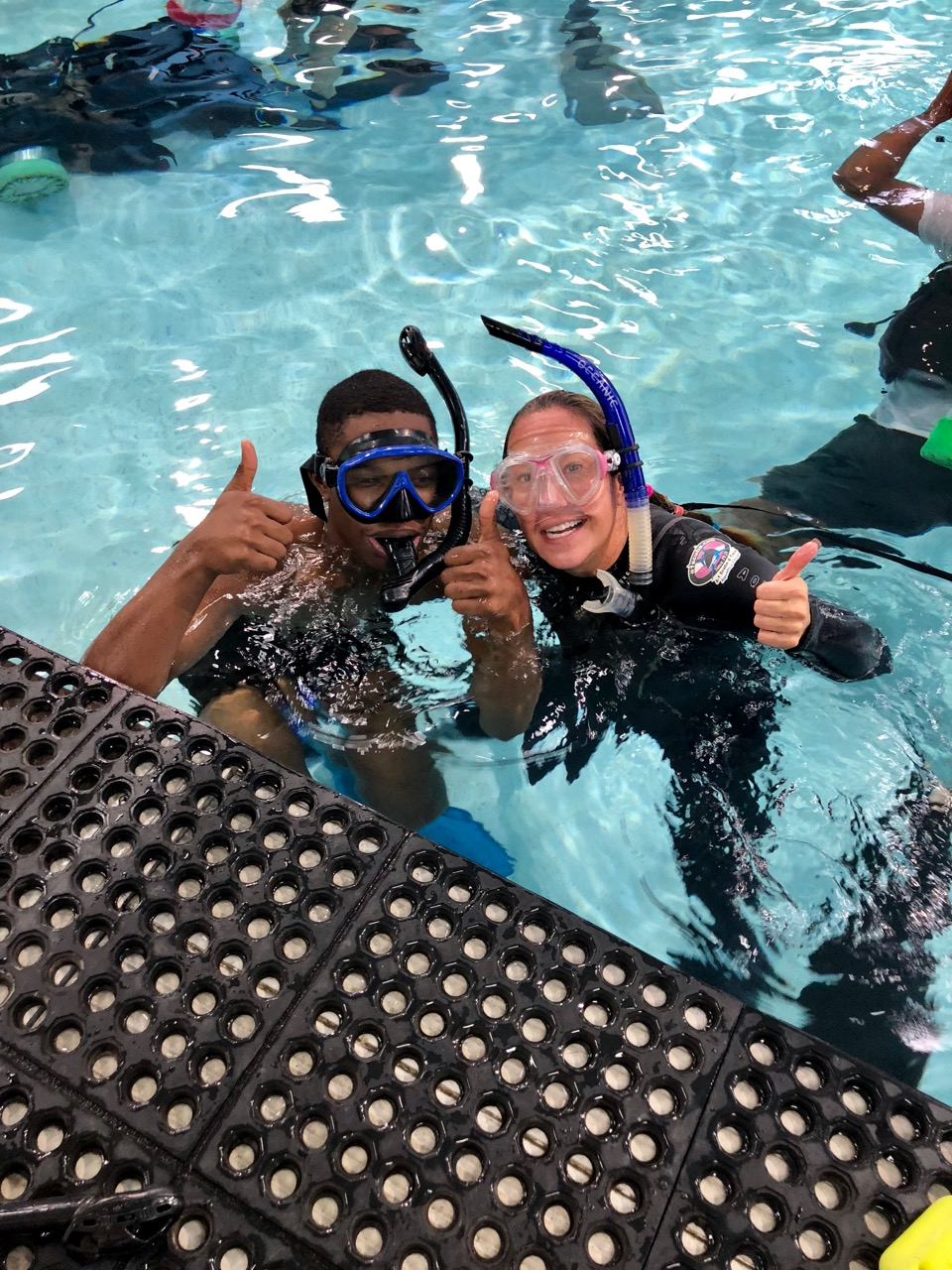 A young man in diving mask and snorkel gives the thumbs up after surfacing with his instructor