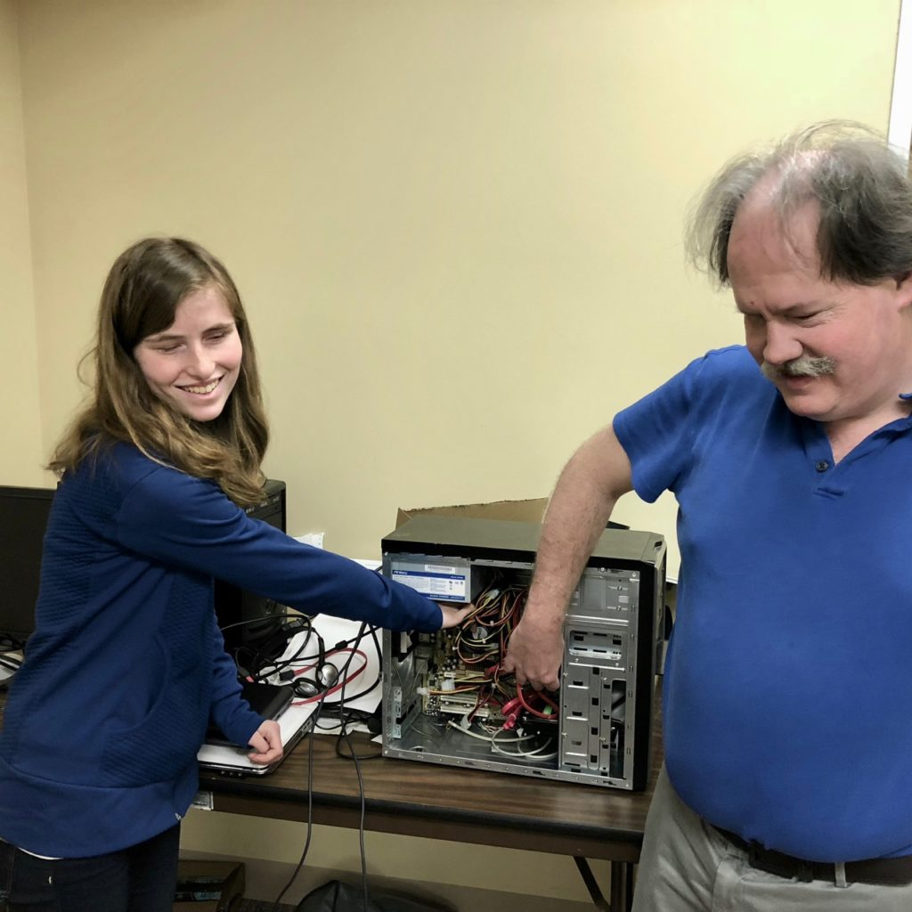 Smiling student explores the inside of a computer with her instructor