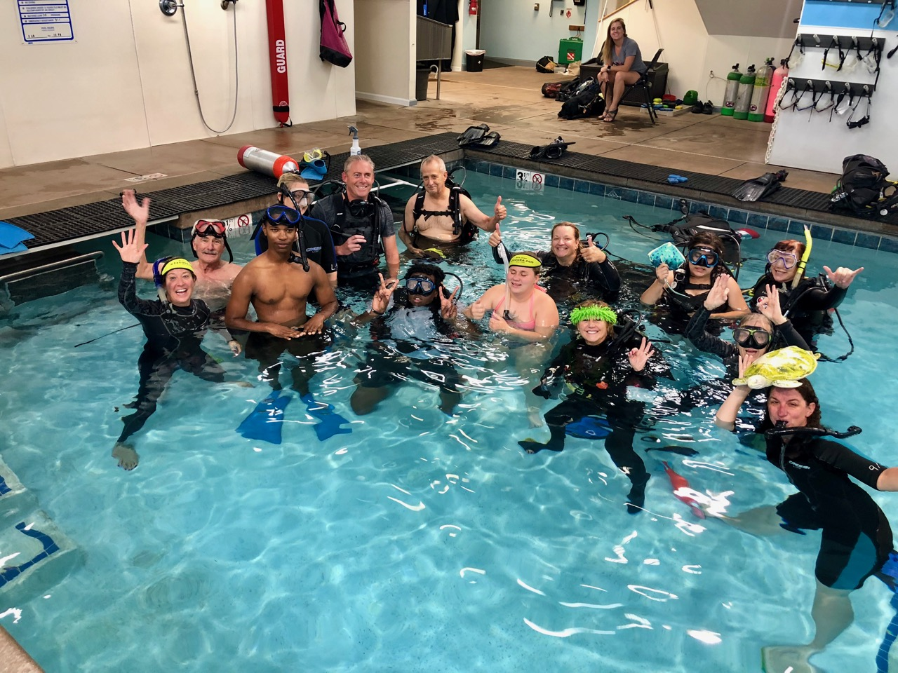 Group of 14 in Scuba Gear in the corner of the pool smile and wave