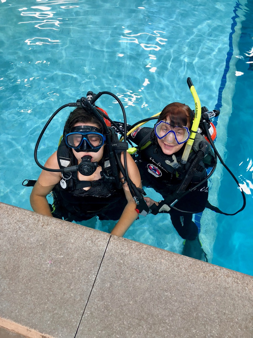 Two women at the surface of a pool with diving masks pushed onto their foreheads