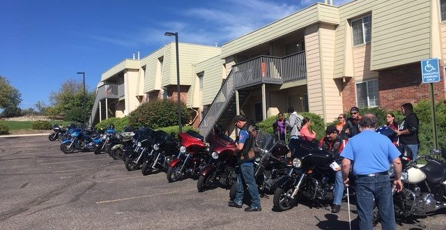 CCB students and staff gather near a row of motorcycles lined up in front of the McGeorge Mountain Terrace Apartments