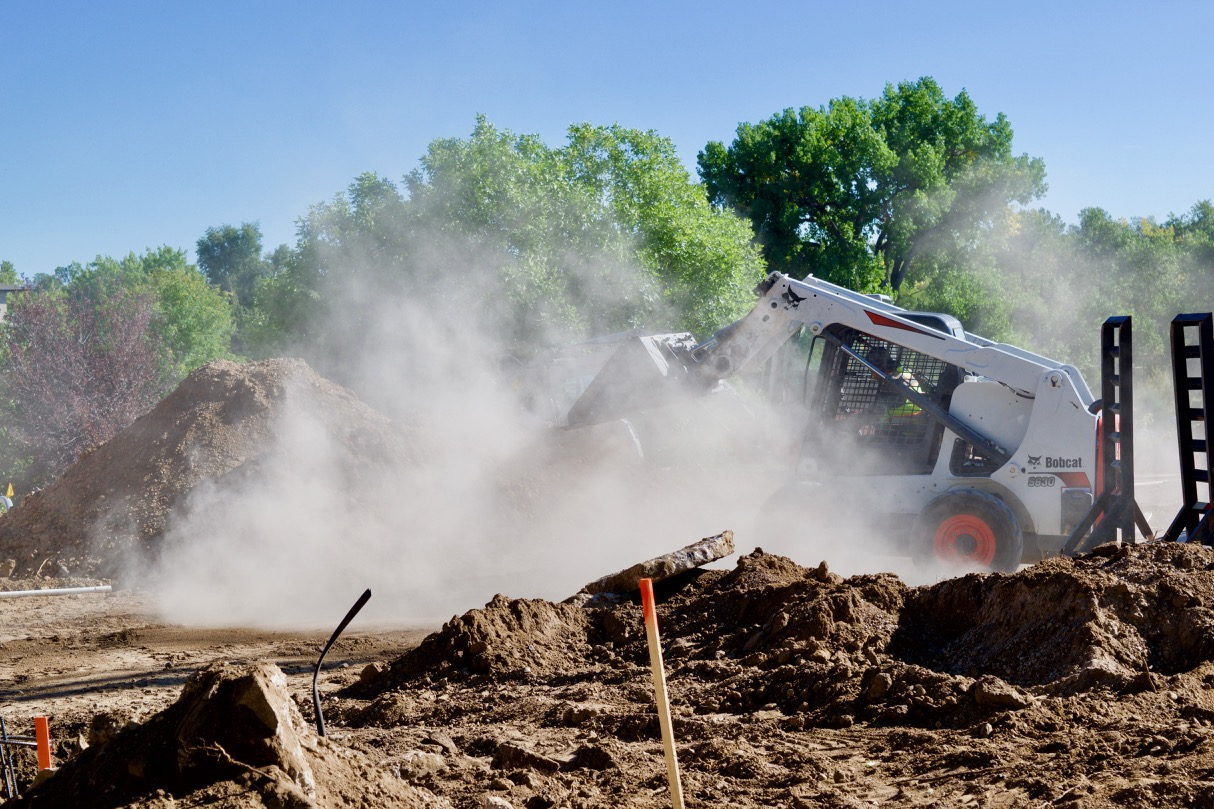 Dust clouds swirl around a front-end loader as dirt and debris are moved for our parking lot construction