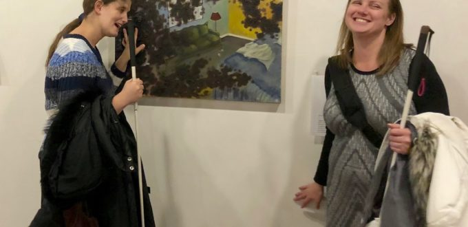 Jen looks at a tactile painting while Stefanie reads the Braille description