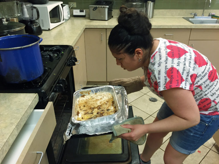 A student uses a pot holder and oven mitt to take a large hot pan with Peach Cobbler out of the oven.