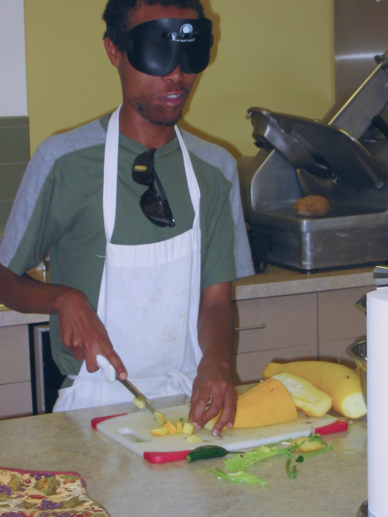 A student slices yellow squash on a cutting board.