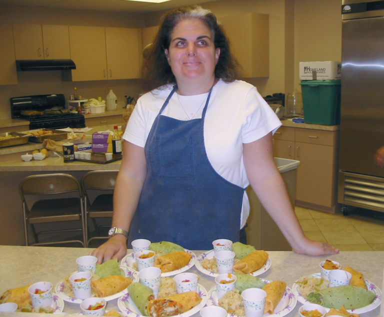 A student proudly displays a dozen plates beautifully arranged for an upcoming meal.