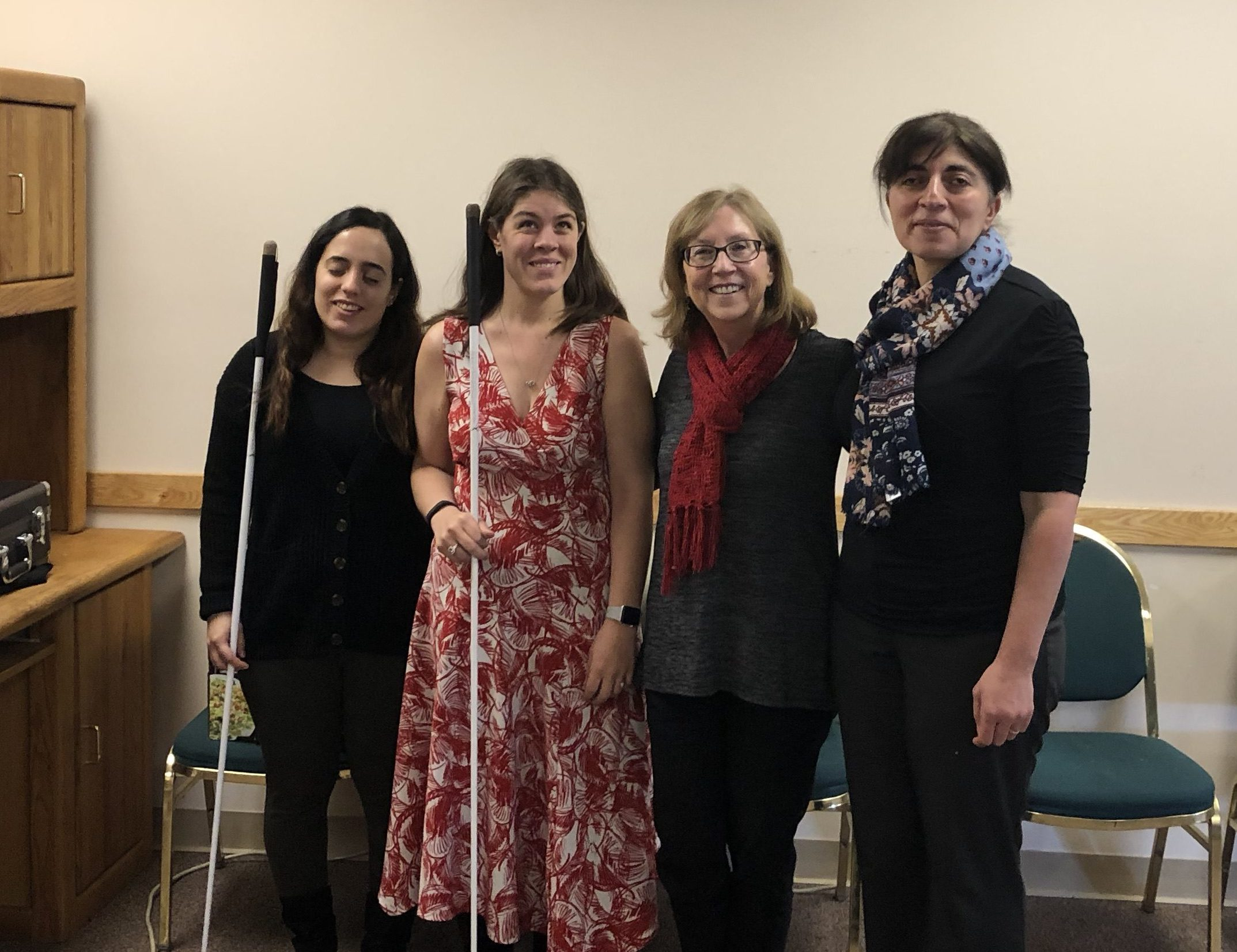 Four smiling women stand together in the Senior Resource Room