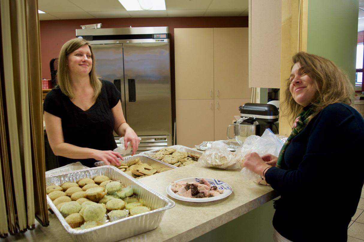 Stephanie P. and Delfina arrange trays of home made cookies, candy, muffins and other treats before breakfast