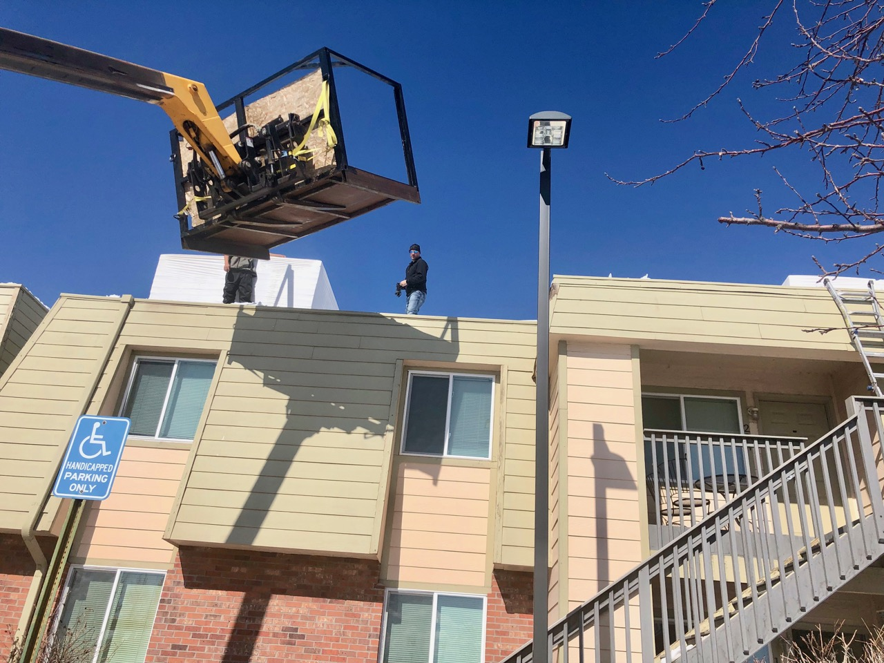 Roofing crew on top of McGeorge Mountain Terrace Apartments with snow blowers