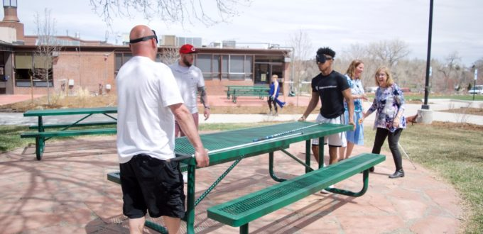 Omar, Charles and Kameron move picnic tables while Julie and Duncan figure out placement